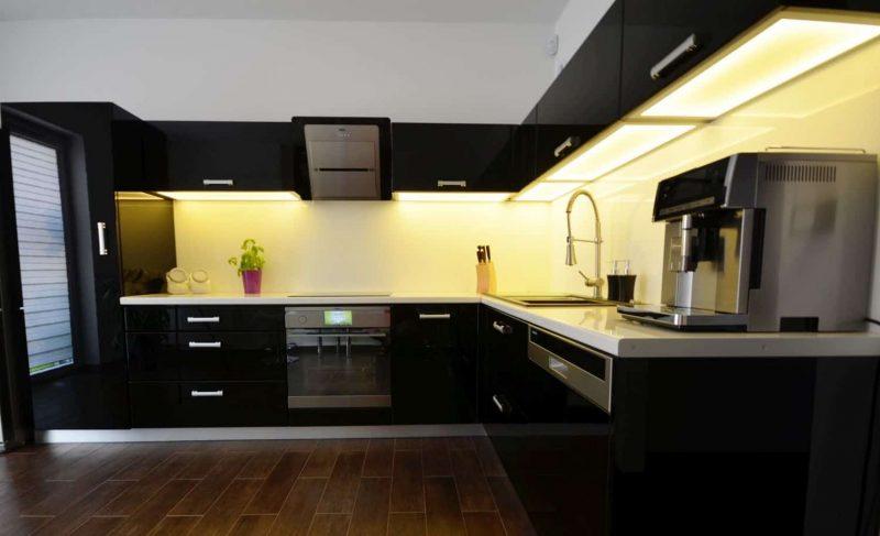 Podświetlenie blatu w nowoczesnej czarnej kuchni.